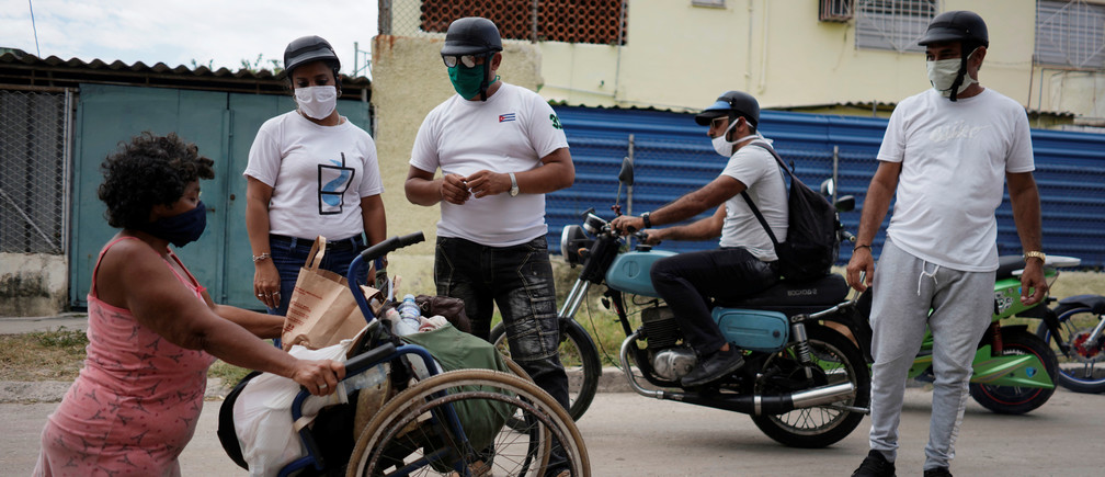 Bikers deliver donated food to a woman with a disability in Havana, Cuba.