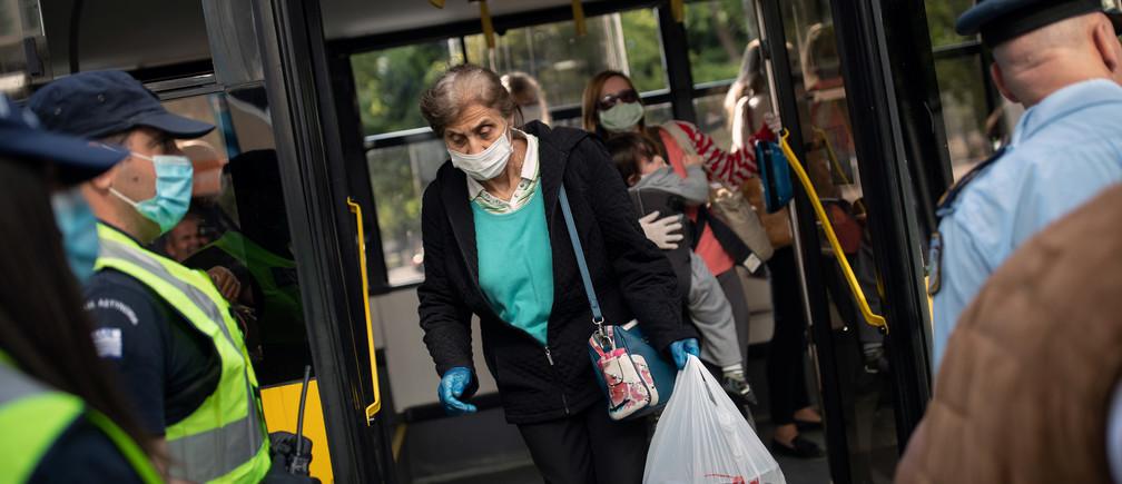 Los agentes de policía esperan para realizar controles a los pasajeros de los autobuses tras el uso obligatorio de mascarillas protectoras, en el primer día de la flexibilización de un bloqueo nacional contra la propagación de la enfermedad coronavirus (COVID-19), en Atenas, Grecia, el 4 de mayo de 2020.