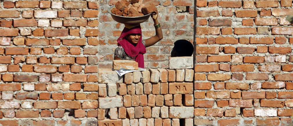 A construction labourer carries bricks on her head at the construction site of a residential estate on the outskirts of the western Indian city of Ahmedabad, November 18, 2011. REUTERS/Amit Dave(INDIA - Tags: SOCIETY BUSINESS EMPLOYMENT CONSTRUCTION) - GM1E7BJ014501
