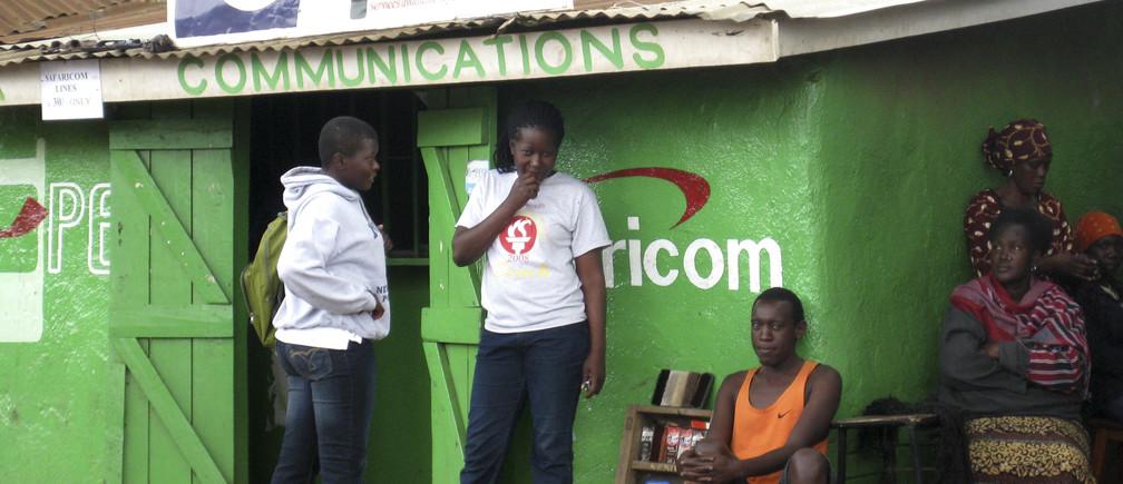 Residents sit outside a Safaricom retail stall in Nairobi's Kibera slum