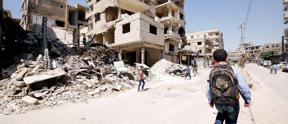 A student walks along a damaged street in the town of Kafr Batna, in eastern Ghouta, Syria September 5, 2018. REUTERS/Omar Sanadiki - RC189D854520