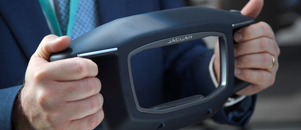 A visitor holds Sayer, a fully voice activated AI concept steering wheel at the Jaguar Land Rover Tech Fest in London in September.