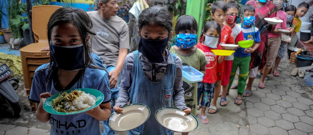 Locals wearing protective masks carry plates while queueing for food distributed for free amid the spread of coronavirus disease (COVID-19) outbreak in Bandung, West Java province, Indonesia, April 10, 2020 in this photo taken by Antara Foto.  Antara Foto/Raisan Al Farisi/ via REUTERS  ATTENTION EDITORS - THIS IMAGE WAS PROVIDED BY A THIRD PARTY. MANDATORY CREDIT. INDONESIA OUT. - RC2L1G9RXUT8
