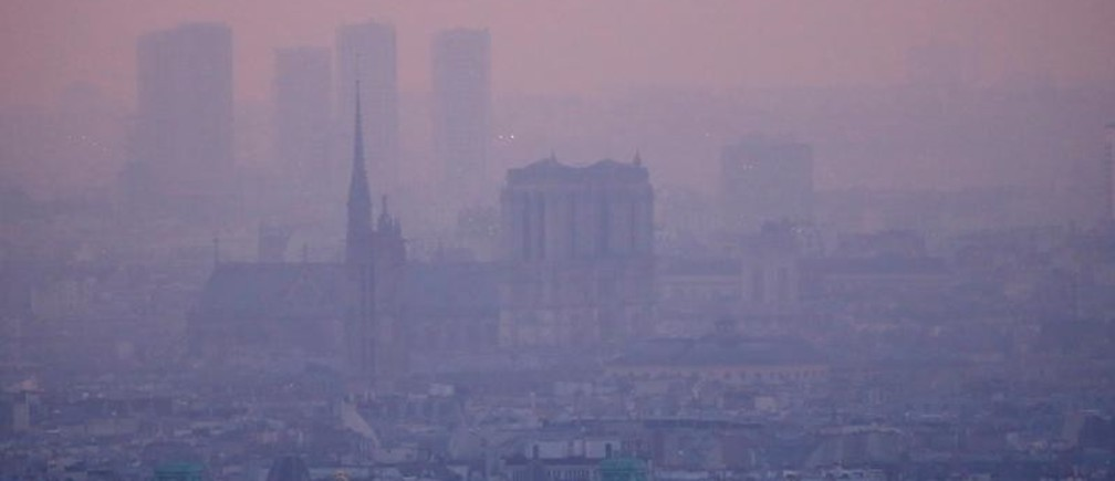 A small-particle haze hangs above the skyline in Paris, France, December 9, 2016 as the City of Light experienced the worst air pollution in a decade. At L, the Notre Dame Cathedral. REUTERS/Gonzalo Fuentes - RC1F9C0FFE10