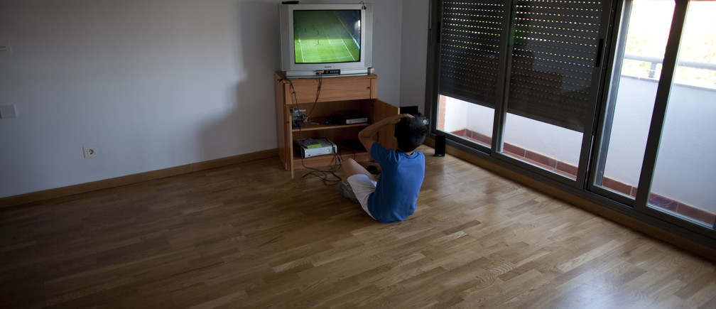 Guillermo, a son of unemployed Aguasanta Quero, 38, plays a video game in the apartment where they live in the Andalusian capital of Seville, southern Spain May 23, 2012. More than 30 struggling families are occupying an apartment in Seville in southern Spain that has been empty since it was finished three years ago. The building is one of hundreds of thousands of ghost constructions gathering dust all over Spain that banks and property developers are unable to sell. Most of the occupiers of the flats, which have brand-new wooden floors with sparkling double glazing, have been thrown out of their own homes by landlords or bailiffs after they defaulted on their mortgage or could not pay the rent.   Picture taken May 23, 2012.          REUTERS/Marcelo del Pozo (SPAIN - Tags: BUSINESS SOCIETY) ATTENTION EDITORS - PICTURE 8 OF 30 FOR PICTURE PACKAGE 'SPAIN'S AUSTERITY SQUATTERS' - GM1E85S1FXY01