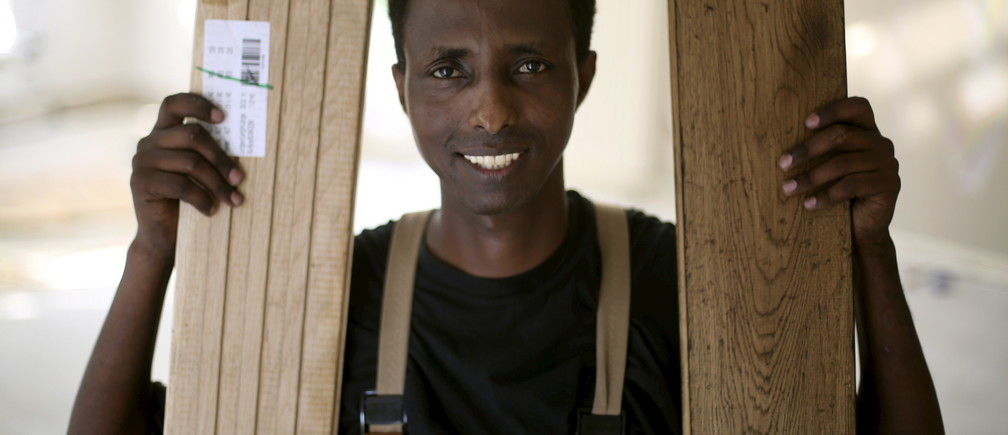 Tesfagebriel Abraha of Eritrea, 31, poses during his apprenticeship for a parquet recliner in Dortmund, Germany, August 31, 2015. Abraha was sent to Daniel Kok, owner of a small flooring business in the west German city of Dortmund, who had been searching for a suitable trainee for over a year when the local trades association asked if he would take on an asylum-seeker. After a successful two-week trial in late July, he is now doing an apprenticeship that lasts until 2018. Picture taken August 31, 2015. To match Analysis EUROPE-MIGRANTS/GERMANY-TRAININGREUTERS/Ina Fassbender - GF10000188790