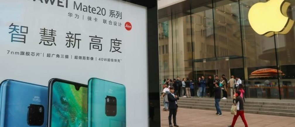 An advertisement for Huawei Mate 20 series is seen outside an Apple store, as customers queue before the store opens on the day the new iPhone XR goes on sale in Shanghai, China October 26, 2018. REUTERS/Stringer  ATTENTION EDITORS - THIS IMAGE WAS PROVIDED BY A THIRD PARTY. CHINA OUT. - RC124178F9F0