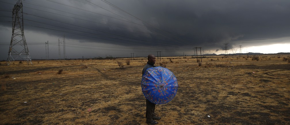 "A striking mineworker holds an umbrella as he awaits a ""report back"" meeting near Lonmin's Marikana mine in South Africa's North West Province, September 6, 2012."