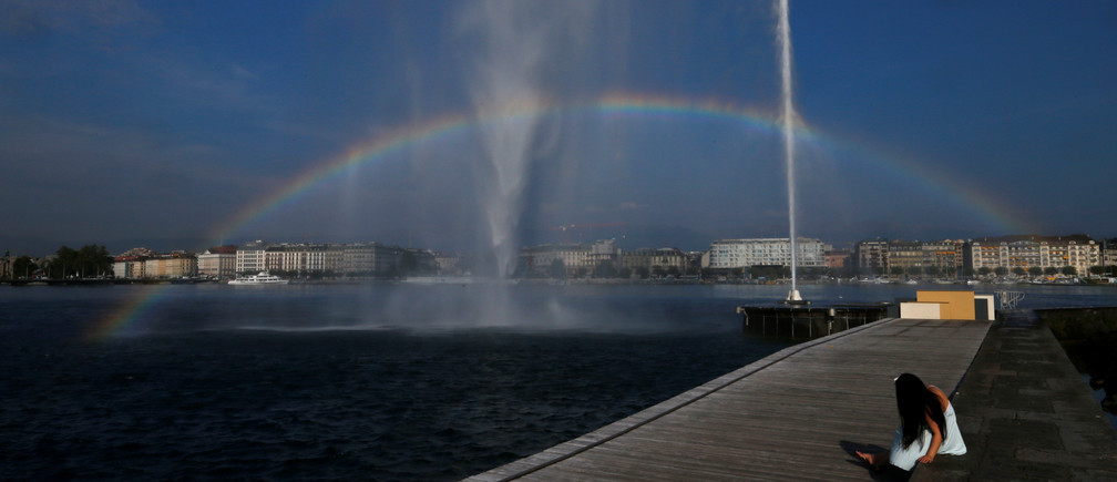 A woman takes a picture of the stream of water of the jet d'eau (water fountain) in Geneva, Switzerland, September 14, 2016.