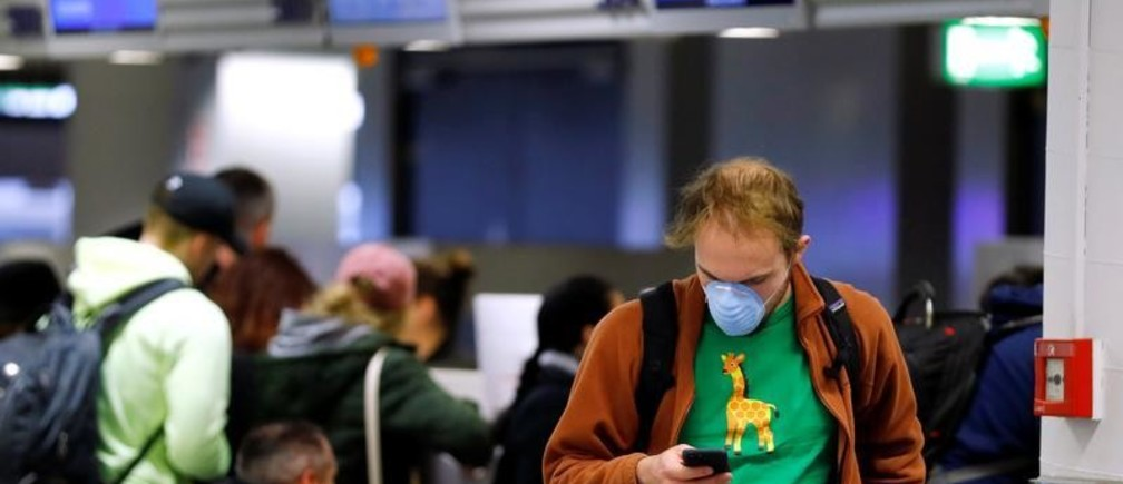 A flight passenger, standing at a ticket counter of U.S. carrier United Airlines, wears a protective mask at Frankfurt Airport, Germany, March 12, 2020.   REUTERS/Ralph Orlowski - RC2DIF90IUOQ