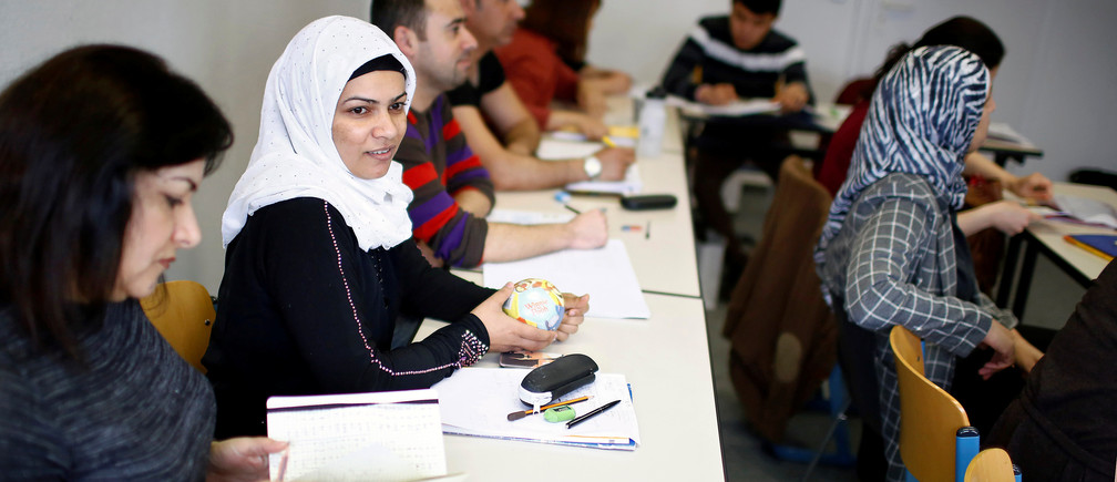 Migrants attend a lesson at the 'Institute for Intercultural Communication' in Berlin