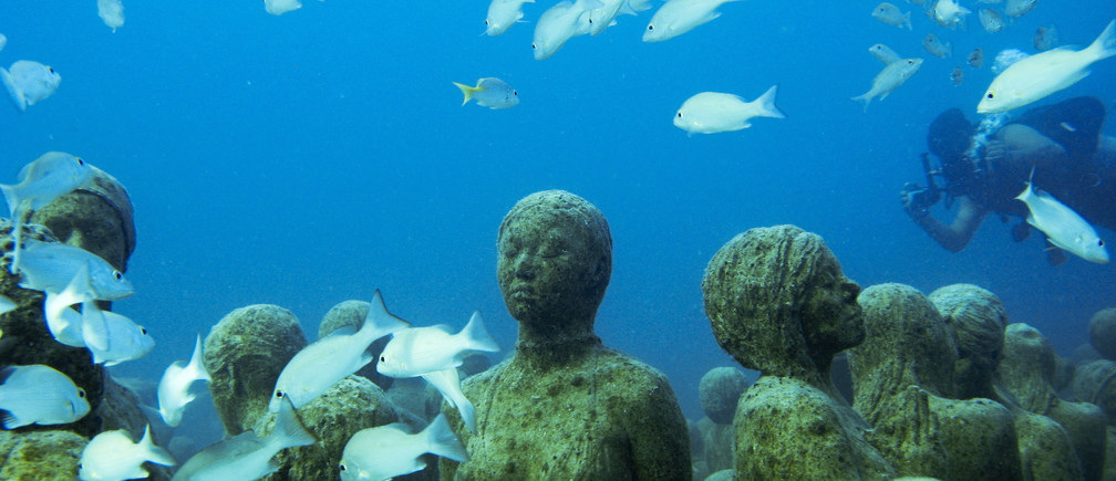 """An underwater sculpture installation """"The Silent Evolution"""" by British artist Jason de Caires Taylor is seen between Cancun and Isla Mujeres December 11, 2010. Taylor used 'life casts' made from materials that encourage coral growth to build the installation on the sea bed off the coast of Cancun. The installation will form a new home for a variety of aquatic creatures at the Cancun and Isla Mujeres National Marine Park and is designed to reduce the impact over half a million tourists have on the area's natural reefs every year, the artist said. Picture taken December 11, 2010. REUTERS/Jorge Silva"""