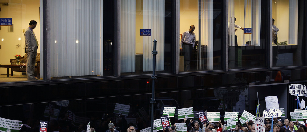 Workers from the Bank of India watch from a window as Occupy Wall Street protesters march 47th Street in New York September 17, 2013. Two years after getting its start in a downtown Manhattan park, Occupy Wall Street, the populist movement protesting economic inequality, marked its second anniversary on Tuesday with a protest near the New York Stock Exchange and a planned march near the United Nations. REUTERS/Joshua Lott (UNITED STATES - Tags: POLITICS CIVIL UNREST)         FOR BEST QUALITY IMAGE ALSO SEE: GF2E9B919UV01 - GM1E99I0PQU01