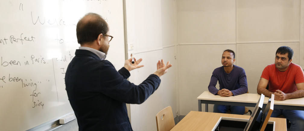 Teacher George Ferenci (L) speaks to asylum seekers Minawar Ahmadzai from Afghanistan (R) and Mohammed Salah Uddin Ahmed from Bangladesh (C) during an English class for refugees at Paris' Sciences Po university in Paris, France, March 15, 2016.