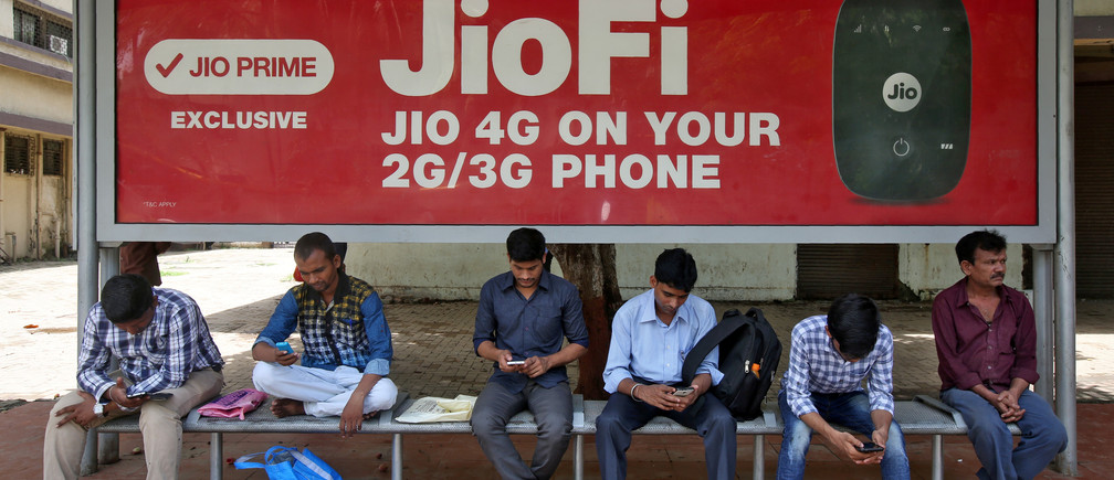 Commuters use their mobile phones as they wait at a bus stop with an advertisement of Reliance Industries' Jio telecoms unit, in Mumbai, India July 10, 2017. REUTERS/Shailesh Andrade - RC1790FB7C60