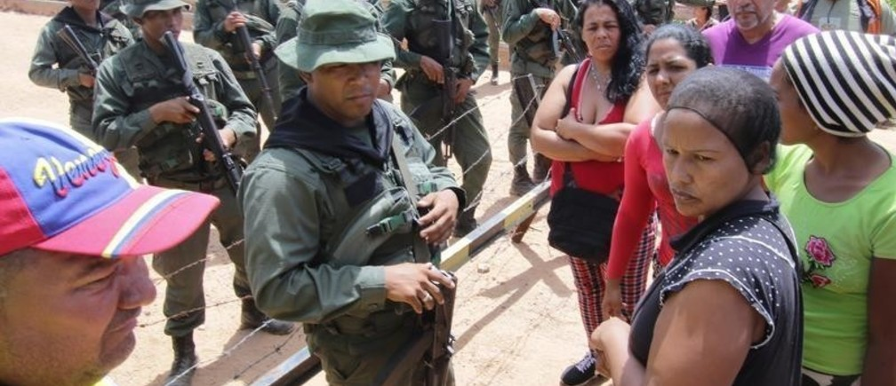 People stand next to Venezuelan soldiers, as they wait for information about the deaths in a remote illegal mine where seven people were killed, according to family members, near the Tarabay military base in Tumeremo, Venezuela October 17, 2018.