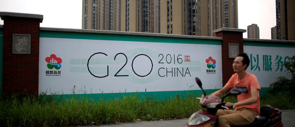A man rides an electronic bike past a billboard for the upcoming G20 summit in Hangzhou, Zhejiang province, China