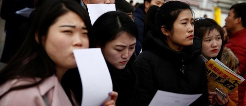 Job seekers look at offers at an open air job fair for college graduates and the general public in the centre of Shijiazhuang, Hebei province, China, February 6, 2017.  REUTERS/Thomas Peter - RTX2ZS3N