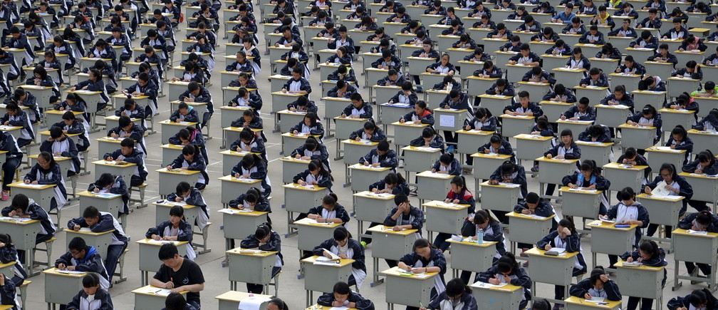 Students take an examination on an open-air playground at a high school in Yichuan, Shaanxi province April 11, 2015. More than 1,700 freshmen students took part in the exam on Saturday, which was the first attempt by the school to take it in open-air. The school said the reasons was due to the insufficient indoor space and also that it could be a test of the students' organizing capacity, local media reported. Picture taken April 11, 2015. REUTERS/Stringer      TPX IMAGES OF THE DAY      - GF10000056535