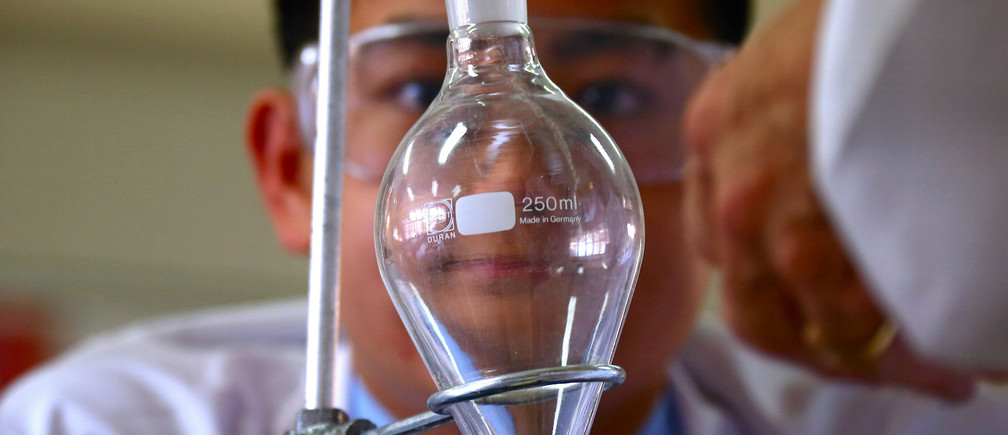 Chemistry student Brandon Lee watches as his classmates prepare to make the compound found in an anti-parasitic medicine used to treat malaria, called Daraprim, in their school lab at Sydney Grammar School in Sydney, Australia December 2, 2016. REUTERS/David Gray - RC15E4DE21C0