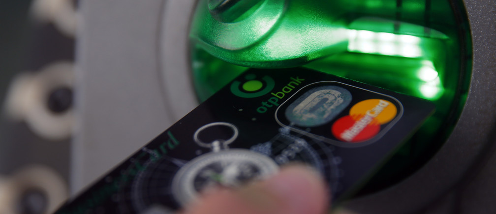 A customer performs a transaction on an ATM at a branch of Hungary's largest lender OTP Bank in central Budapest July 24, 2013.