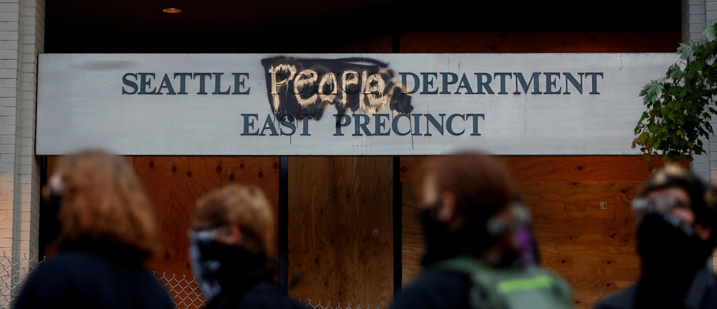 "People stand in front of the Seattle Police Department's East Precinct sign, spray painted to replace ""police"" with ""people"" as the protesters established what they call an autonomous zone while continuing to demonstrate against racial inequality and call for defunding of Seattle police, in Seattle, Washington, U.S. June 9, 2020. Picture taken June 9, 2020. REUTERS/Lindsey Wasson     TPX IMAGES OF THE DAY - RC276H9WJ22I"