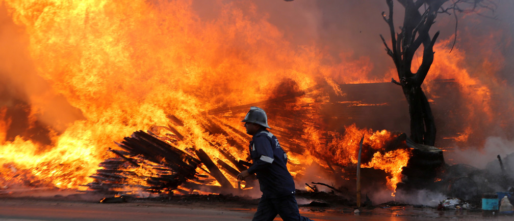 A firefighter runs past a burning tree and wooden packaging material after a fire broke out at a wood store in Ahmedabad, India, March 24, 2019. REUTERS/Amit Dave - RC128C1E4710