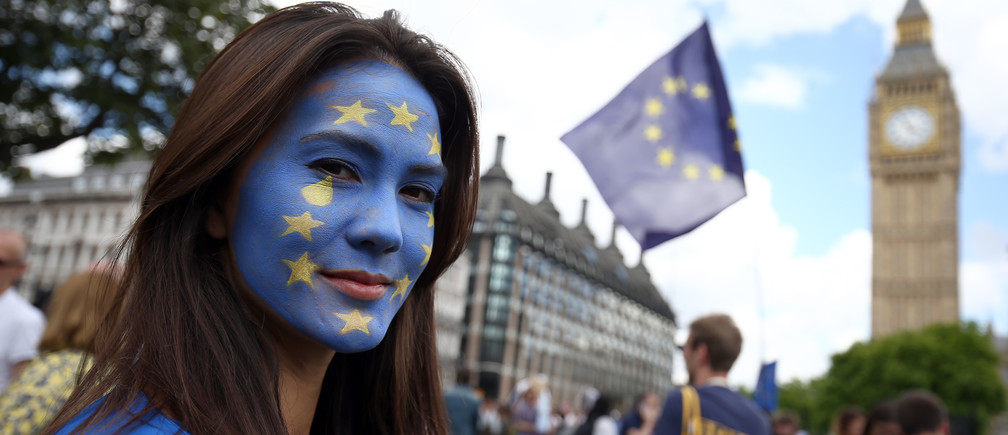 A woman with a painted face poses for a photograph during a demonstration against Britain's decision.