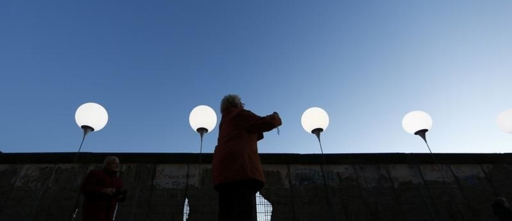 An elderly woman takes a picture of lit balloons at the former Berlin Wall location near Friedrichstrasse in Berlin November 8, 2014. A part of the inner city of Berlin will be temporarily divided from November 7 to 9, with a light installation 'Lichtgrenze' (Border of Light) featuring 8000 luminous white balloons to commemorate the 25th anniversary of the fall of the Berlin Wall.          REUTERS/Michael Dalder (GERMANY  - Tags: POLITICS ANNIVERSARY SOCIETY)   - RTR4DCZG
