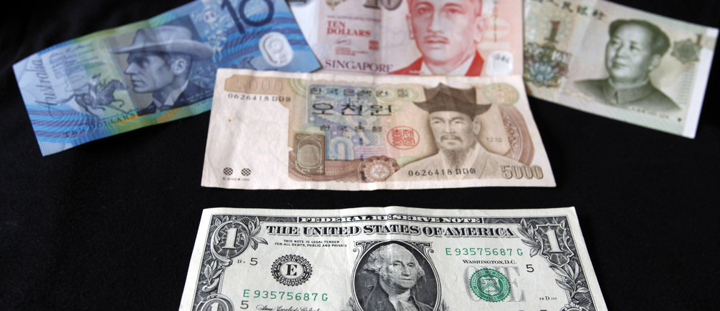 A U.S. dollar note (bottom) is pictured alongside other currencies including (L-R) the Australian Dollar, Singapore Dollar, Korean Won and China's Yuan in this picture illustration taken in Washington, October 14, 2010.  The U.S. dollar index hit the year's low and world stocks were modestly higher on Thursday after Singapore let its currency strengthen, spurring gains in most major currencies against the struggling greenback. The Australian dollar, which boasts the highest yield among major currencies, soared to a 28-year high at $0.9994, and poised to near parity.   REUTERS/Jason Reed   (UNITED STATES - Tags: BUSINESS) - GM1E6AF05WS01