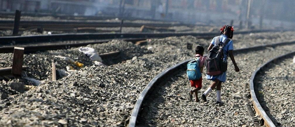 School children walk on railway tracks in Mumbai February 13, 2009.