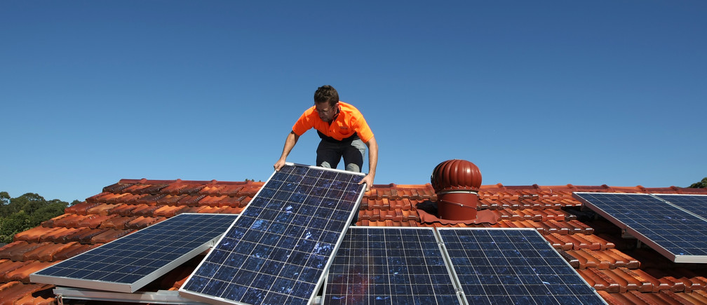 Solar system installer Thomas Bywater adjusts new solar panels on the roof of a house in Sydney August 19, 2009.  REUTERS/Tim Wimborne    (AUSTRALIA ENVIRONMENT ENERGY) - GM1E58J161901