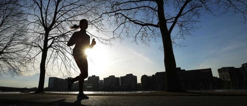 A woman jogs along the Charles River on an early spring evening in Boston, Massachusetts April 3, 2014. REUTERS/Brian Snyder  (UNITED STATES - Tags: SOCIETY ENVIRONMENT)