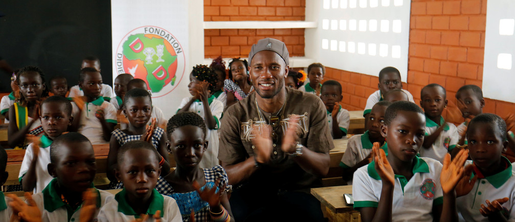 Ivory Coast's former soccer player Didier Drogba applauds with pupils in a classroom of a school built by the Didier Drogba Foundation at Pokou Kouamekro, Gagnoa, Ivory Coast, January 17, 2018. REUTERS/Thierry Gouegnon - RC1213683740