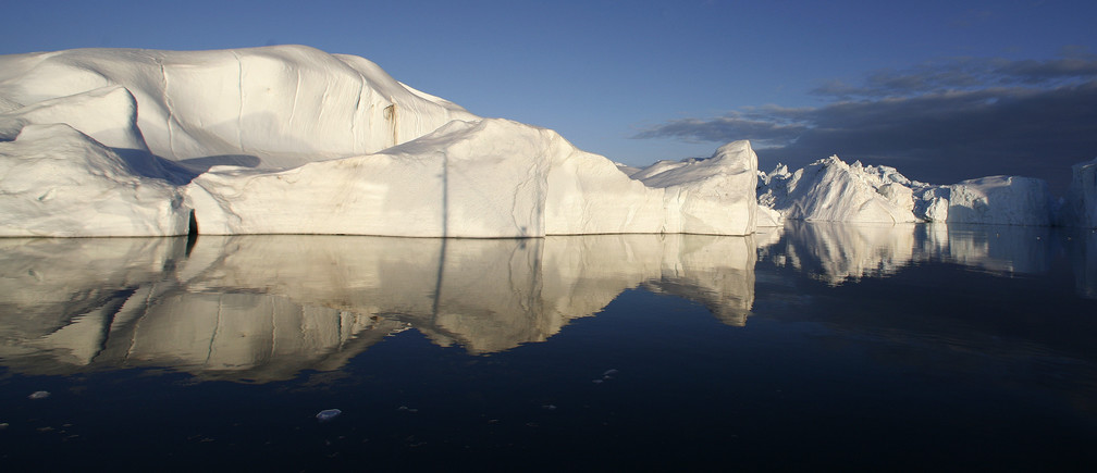 Icebergs are reflected in the calm waters at the mouth of the Jakobshavn ice fjord near Ilulissat in Greenland in this photo taken May 15, 2007. New York, Boston and other cities on North America's northeast coast could face a rise in sea level this century that would exceed forecasts for the rest of the planet if Greenland's ice sheet keeps melting as fast as it is now, researchers said May 27, 2009. Sea levels off the northeast coast of North America could rise by 12 to 20 inches more than other coastal areas if the Greenland glacier-melt continues to accelerate at its present pace, the researchers reported.    REUTERS/Bob Strong/Files