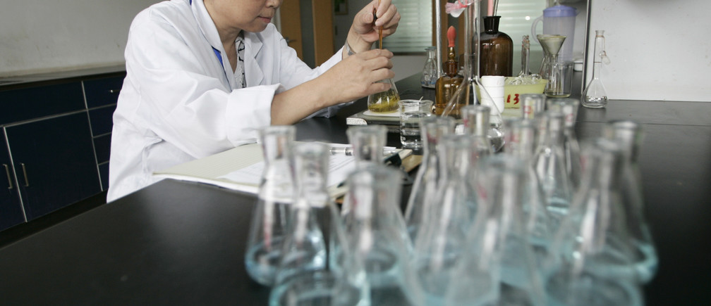 """A laboratory worker tests vegetable sample at the Supervision and Testing Center for Vegetable Quality of Ministry of Agriculture in Beijing August 2, 2007. China defended the """"made-in-China"""" label on the eve of Asia's largest security forum on Wednesday and the United States said it attached great importance to the region despite the absence of its top foreign policy official. REUTERS/Alfred Cheng Jin (CHINA) - GM1DVVLCQXAA"""