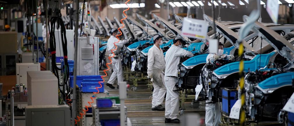 Los empleados trabajan en una línea de producción dentro de una fábrica de Dongfeng Honda después de que las medidas de cierre en Wuhan, la capital de la provincia de Hubei y el epicentro del brote de la nueva enfermedad coronavirus (COVID-19) en China, se suavizaron aún más, el 8 de abril de 2020.