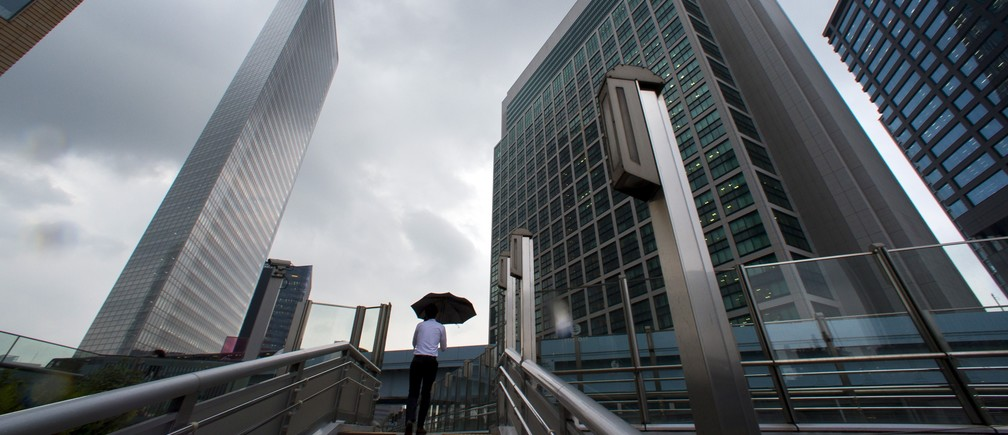 A man walks in the shadows of office skyscrapers in a business district in Tokyo August 20, 2015.