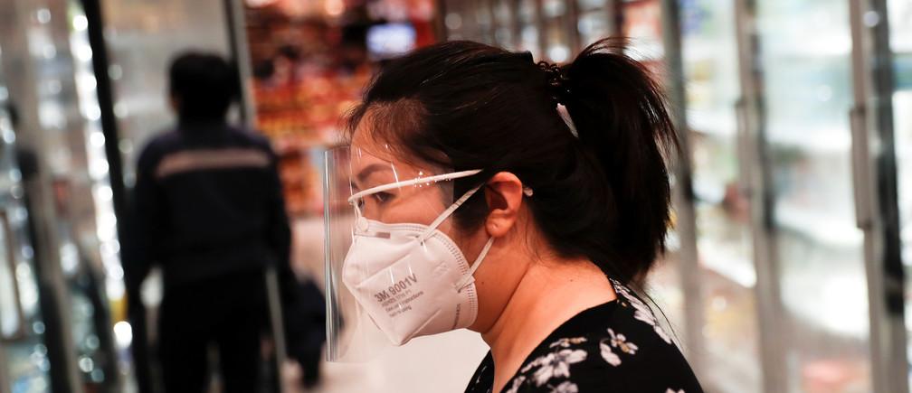 Une femme marche avec un masque de protection et un écran facial à l'intérieur d'un supermarché lors de l'épidémie de coronavirus (COVID-19) à Bangkok, Thaïlande, le 9 avril 2020.