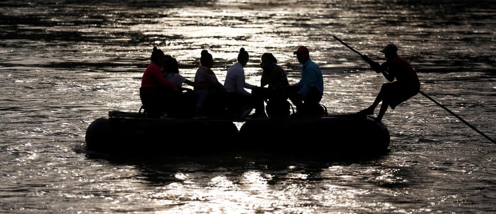 Migrants cross the Suchiate river on a raft from Tecun Uman, in Guatemala, to Ciudad Hidalgo, as seen from Ciudad Hidalgo, Mexico, June 13, 2019. REUTERS/Jose Cabezas - RC1DA319F400