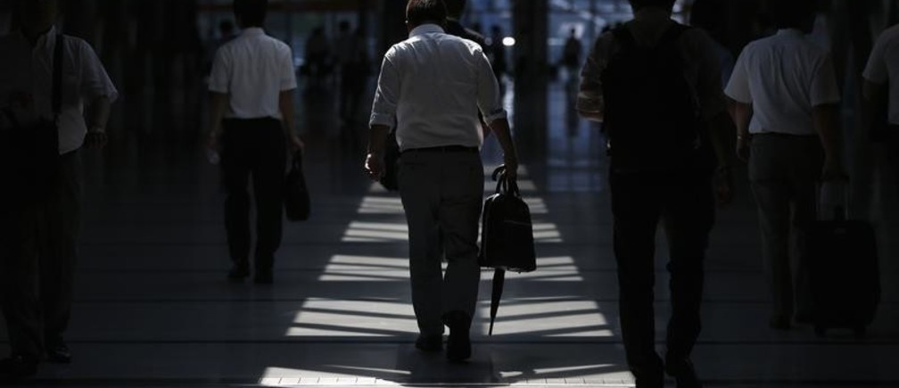 Businessmen walk in a convention centre in Tokyo July 18, 2013. Japanese manufacturers' mood slid in July for the first time in eight months after June had the best reading in more than two years, a Reuters poll showed, as China's slowdown clouded the outlook for the export-reliant economy. REUTERS/Toru Hanai (JAPAN - Tags: BUSINESS INDUSTRIAL) - GM1E97I160P01