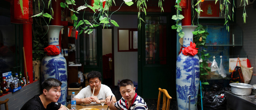 Men eat a Chinese dish that was prepared using oil made from soy beans at a restaurant in Beijing, China, July 3, 2018.  REUTERS/Thomas Peter - RC126E49C3F0