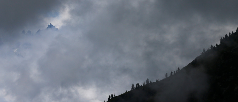 Clouds are seen between peaks and trees in Emosson, Switzerland August 9, 2017. REUTERS/Denis Balibouse - RC13053E6BD0