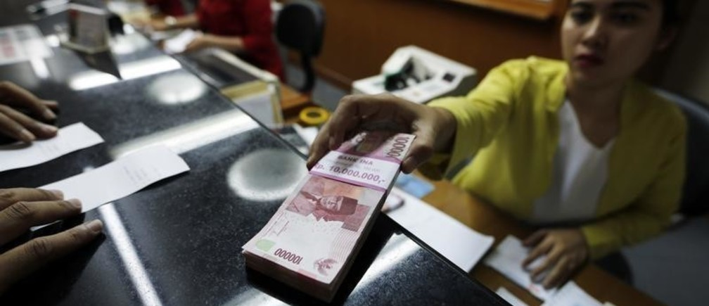 A woman holds Indonesian rupiah notes at a moneychanger in Jakarta, March 17, 2015. Indonesia's central bank, which last month surprisingly cut its benchmark rate, on Tuesday held it steady at 7.50 percent, as expected. Bank Indonesia said the level of the rate is consistent with efforts to contain inflation and the current account deficit.