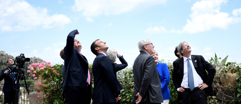 (L-R) U.S. President Donald Trump, French President Emmanuel Macron, Britain's Prime Minister Theresa May, the President of the European Commission Jean-Claude Juncker, German Chancellor Angela Merkel and Italian Prime Minister Paolo Gentiloni watch an Italian flying squadron as part of activities at the G7 Summit in Taormina, Sicily, Italy, May 26, 2017.   REUTERS/Stephane De Sakutin/Pool - RTX37R70