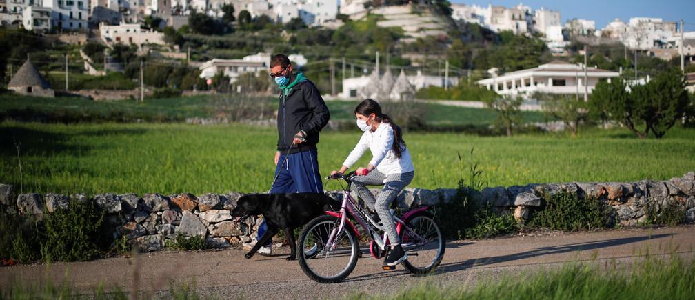 Daniele Perrini pasea a su perro mientras su hija Michela Perrini, de 9 años, pedalea cerca de su casa, en la pequeña ciudad histórica del sur de Cisternino, Italia, el 24 de abril de 2020.