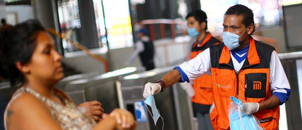 Los empleados entregan máscaras a los pasajeros para su uso obligatorio a partir del próximo viernes, dentro de cualquier estación de metro, como medida para contener la propagación de la enfermedad coronavirus (COVID-19), en la Ciudad de México, México 15 de abril de 2020.