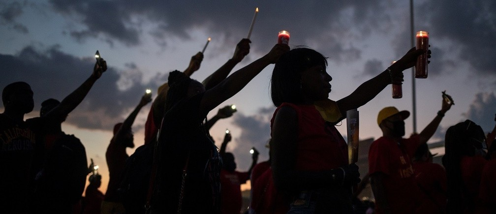 Local residents and alumni of Yates high school take part in a candlelight vigil honoring George Floyd, whose death in Minneapolis police custody has sparked nationwide protests against racial inequality, on the high school field he played football in Houston, Texas, U.S., June 8, 2020. REUTERS/Adrees Latif - RC2E5H9COPP2