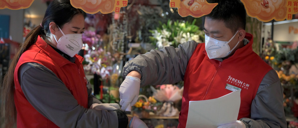 A staff member checks temperature of a staff who has not been checked before the store opens at a JD.com's 7Fresh chain, as the country is hit by an outbreak of the novel coronavirus, in Yizhuang town, Beijing, China February 8, 2020. Picture taken February 8, 2020. REUTERS/Tingshu Wang - RC2XWE9UJHLF