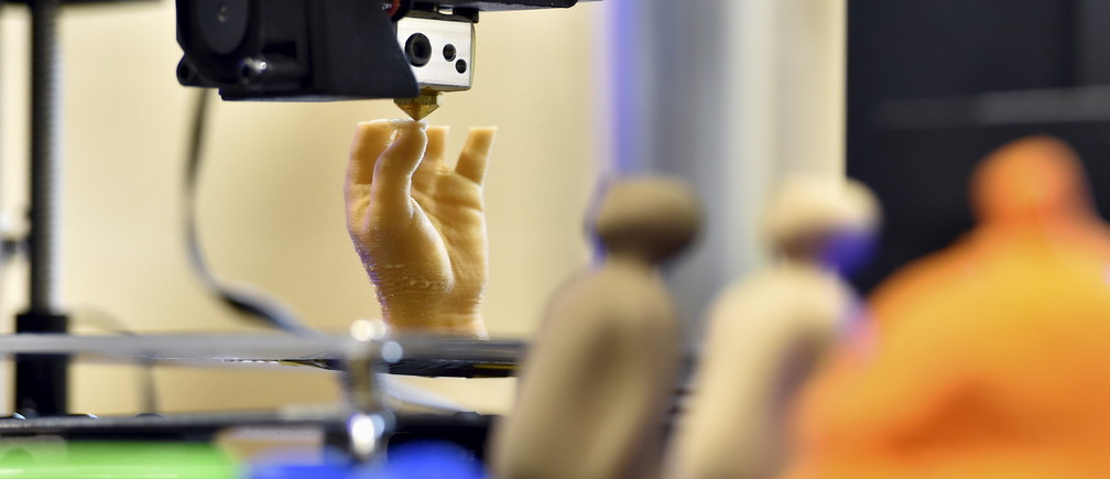 3D printed objects are displayed as an artificial hand is being printed during a 3D printing show in Brussels, Belgium, October 18, 2015.